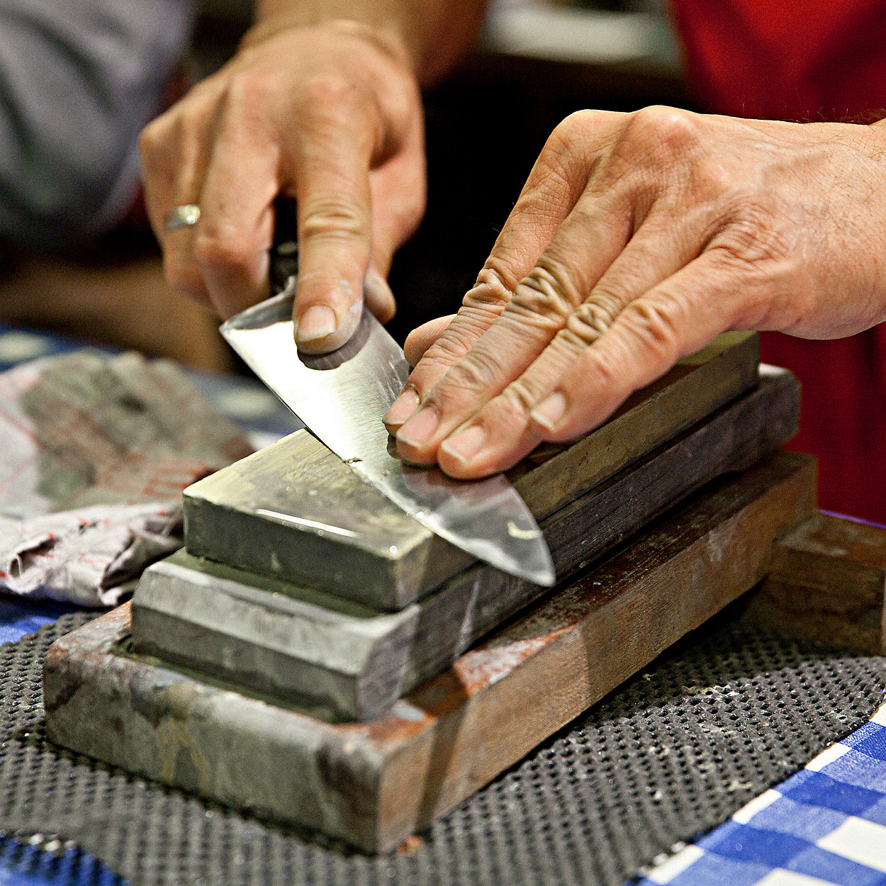 sharpening a kitchen knife on a whetstone